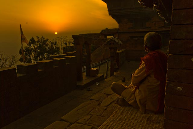 A devotee watches the sun set from the Temple of Goddess Gorakh Kali